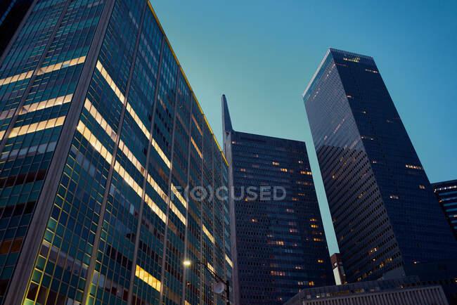 Desde abajo rascacielos modernos con cielo azul en el fondo al atardecer en Dallas, Texas, EE.UU. - foto de stock