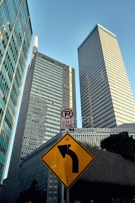 Von unten Verkehrsschilder mit großen modernen Wolkenkratzern und blauem Himmel im Hintergrund — Stockfoto