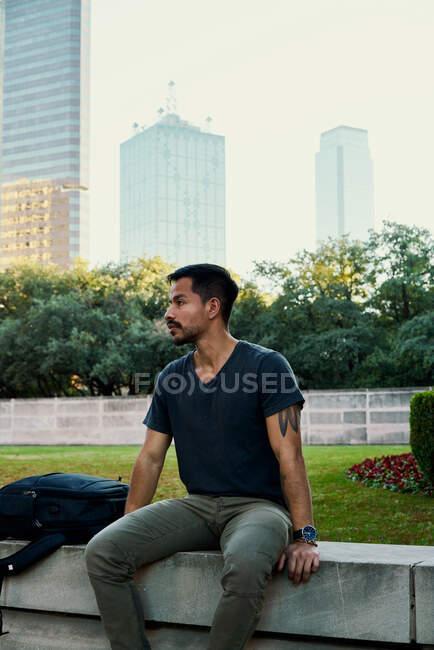 Giovane studente ispanico maschio in elegante abbigliamento casual seduto sulla recinzione a dondolo e guardando lontano con il centro in background a Dallas, Texas — Foto stock
