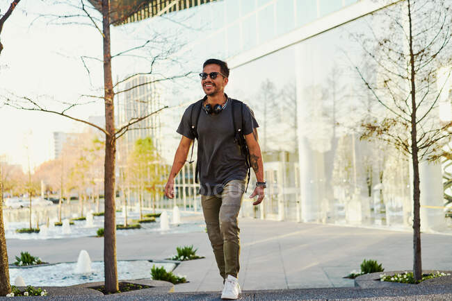 Cheerful bearded Hispanic man in casual outfit smiling and looking away with trendy sunglasses and headphones on neck at city street — Stock Photo