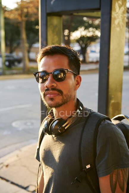 Giovane uomo ispanico in abbigliamento casual e occhiali da sole alla moda con cuffie e zaino guardando la fotocamera in strada della città — Foto stock