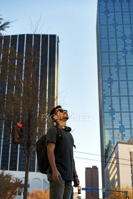 Bearded Hispanic man in casual outfit smiling and looking up with trendy sunglasses and headphones on neck at city street — Stock Photo