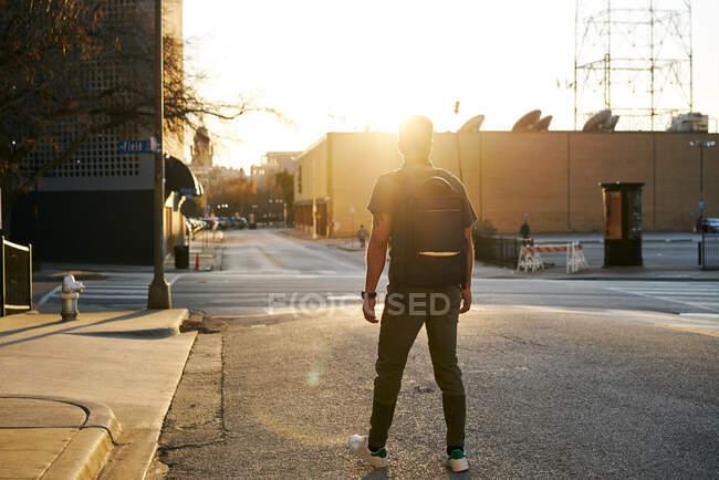 Visão traseira de homem irreconhecível em roupa casual com uma mochila andando em uma rua da cidade durante o pôr do sol — Fotografia de Stock