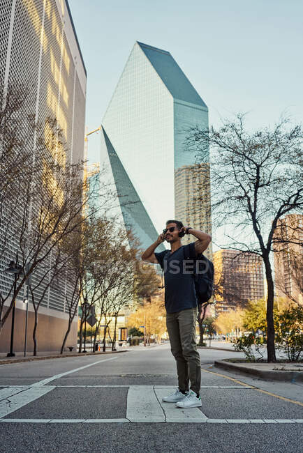 Hispanic male traveler in casual outfit and sunglasses with backpack putting on headphones while sightseeing at downtown — Stock Photo