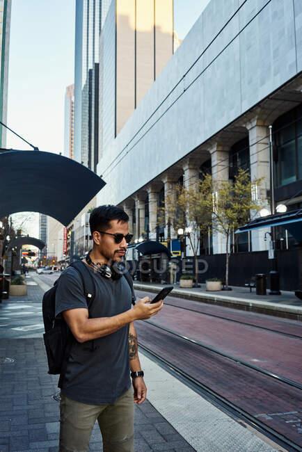 Vue latérale d'un touriste hispanique contemporain en tenue décontractée et lunettes de soleil avec sac à dos et écouteurs utilisant le téléphone portable dans la rue moderne de la ville — Photo de stock