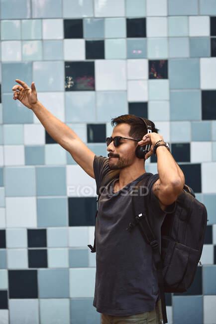 Felice uomo ispanico in abbigliamento casual e zaino con cuffie in piedi ad ascoltare musica in strada — Foto stock