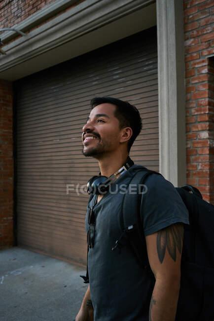 Vista laterale del viaggiatore ispanico maschile in abito casual con zaino in piedi lungo la strada vuota della città con edificio in mattoni sullo sfondo — Foto stock