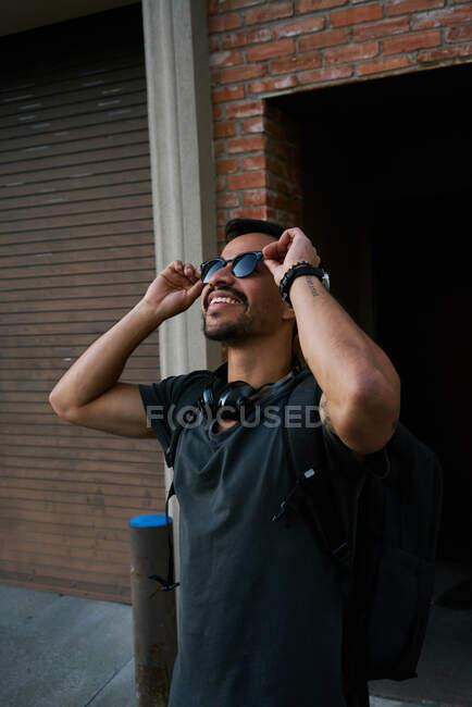 Vista laterale del viaggiatore ispanico maschile in abito casual e occhiali da sole stilista con zaino in piedi lungo la strada vuota della città con edificio in mattoni sullo sfondo — Foto stock