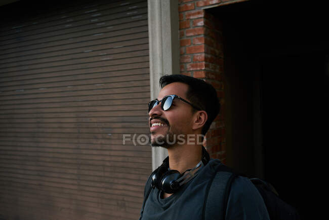 Side view of hispanic male traveler in casual outfit and stylist sunglasses with backpack standing along empty city street with bricked building on background — Stock Photo