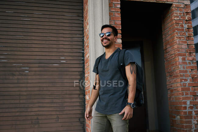 Hispanic male traveler in casual outfit and stylist sunglasses with backpack standing along empty city street with bricked building on background — Stock Photo