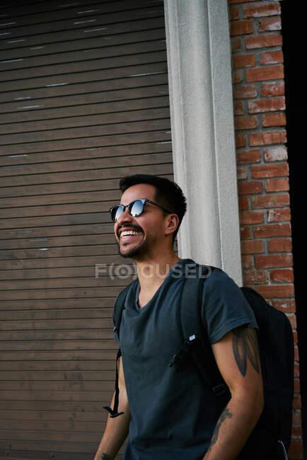 Vista lateral do viajante macho hispânico em roupa casual e óculos de sol estilista com mochila de pé ao longo da rua vazia da cidade com edifício tijolo no fundo — Fotografia de Stock