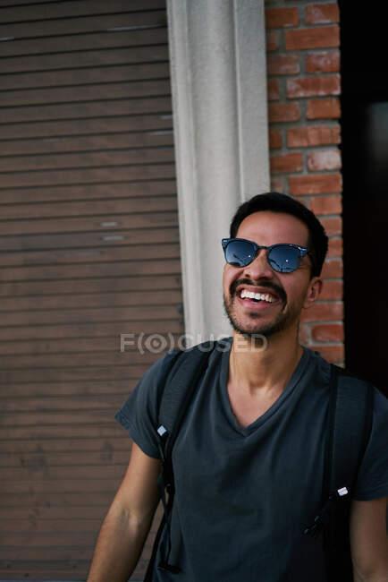 Viaggiatore maschio ispanico in abito casual e occhiali da sole stilista con zaino in piedi lungo la strada vuota della città con edificio in mattoni sullo sfondo — Foto stock