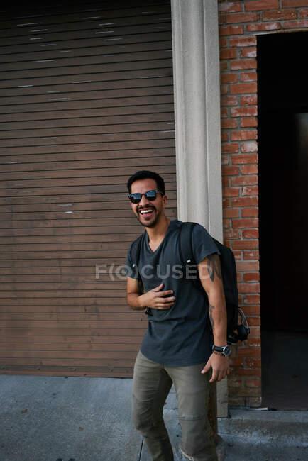 Латиноамериканец в повседневной одежде и стилистские солнцезащитные очки с рюкзаком, стоящим вдоль пустой городской улицы с кирпичным зданием на заднем плане — стоковое фото