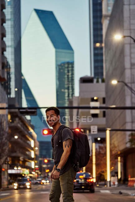 Side view of pleased Hispanic male traveler with backpack in casual outfit laughing while strolling at modern downtown — Stock Photo