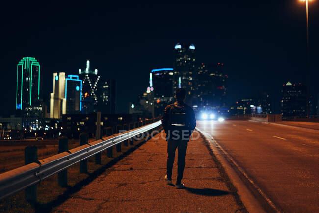 Vue arrière de l'homme anonyme en veste décontractée en cuir noir avec sac à dos marchant la nuit ville sur fond flou — Photo de stock