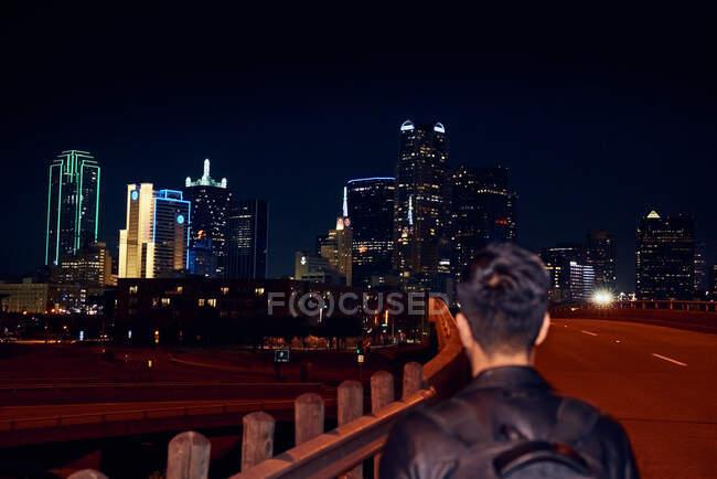 Vista trasera de hombre anónimo en chaqueta de cuero negro casual con mochila caminando por la ciudad de la noche sobre fondo borroso - foto de stock