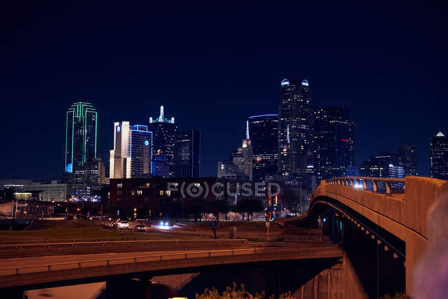 Rocked ponti attraversati vuoti con grattacieli colorati luminosi del centro sotto cielo nero notte — Foto stock
