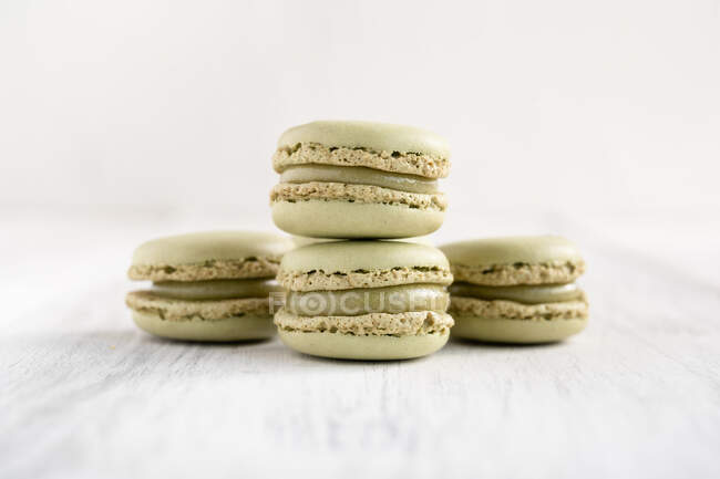 Green tasty macaroons stacked in pile against wooden white surface — Stock Photo