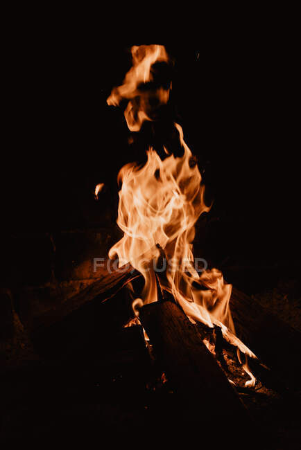Yellow flames rising up from bonfire on wooden pieces in nature at night — Stock Photo
