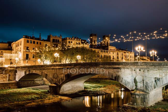 Majestic landscape of ancient illuminated bridge above river reflecting city light in Girona, Catalonia, Spain — Stock Photo
