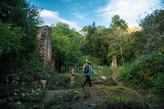 Back view of anonymous active tourist with black backpack moving on path between stones and forest grove — Stock Photo