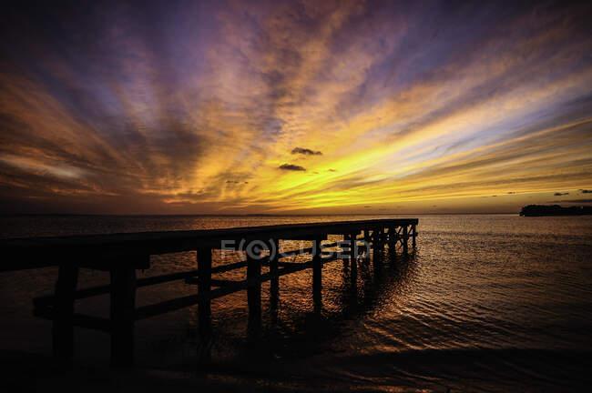 Impresionante paisaje de muelle solitario en el vasto océano bajo el cielo colorido brillante en la puesta del sol - foto de stock