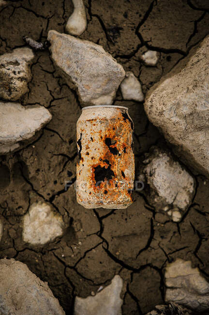 From above rusty shabby old can on cracked dark terrain with stone — Stock Photo