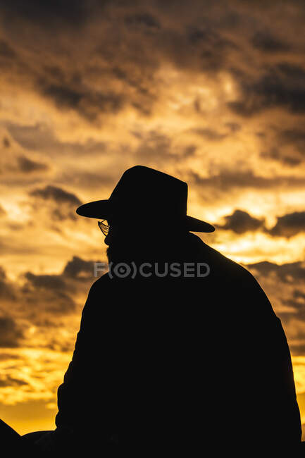 Back view of unrecognizable silhouette of man sitting on roof of building looking at view of city sunset — Stock Photo