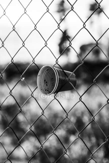 Пустые пластиковые чашки в стене забора безопасности с металлической сеткой в поле — стоковое фото