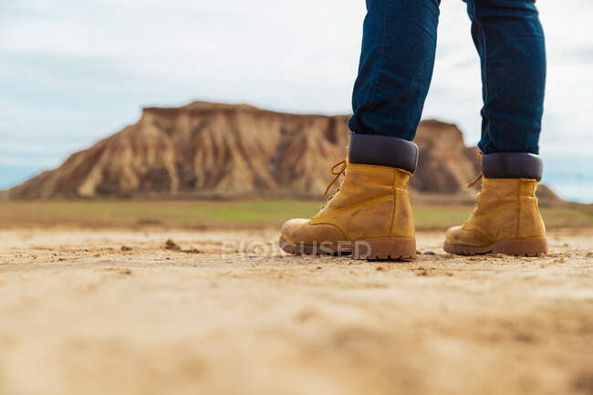 Legs on faceless traveler in brown boots and blue jeans standing on dirty sandy road with mountain and sky on blurred background in Bardenas Reales, Navarre, Spain — Stock Photo