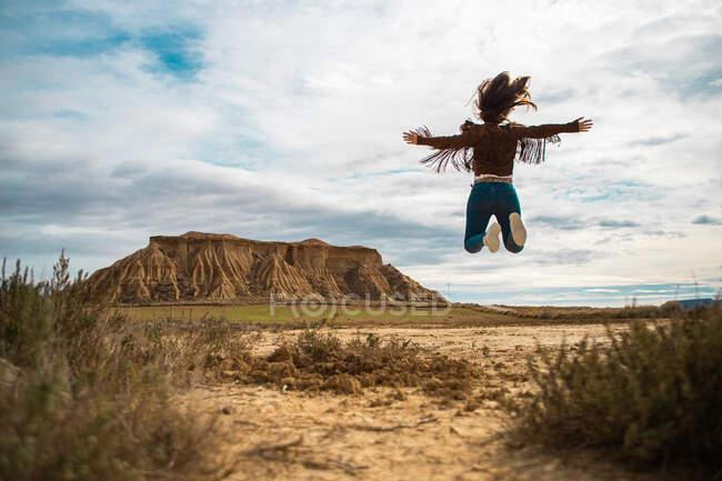 Обратный вид на неузнаваемую даму в отпуске в стильной повседневной одежде, размахивающей руками среди пустынной долины с большой коричневой скалой и голубым небом на заднем плане в Барденас Реалес, Наварра, Испания — стоковое фото
