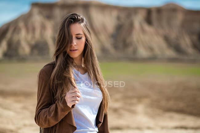 Вдумчивая соблазнительная женщина-путешественница с закрытыми глазами стоит рядом с большой горой и голубым небом на заднем плане в Барденас-Реалес, Наварра, Испания — стоковое фото