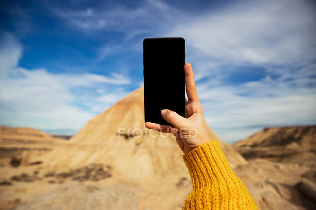 Crop female hands of anonymous traveler taking picture of big brown cliff with colorful blue sky and white clouds on background at Bardenas Reales at Spain — Stock Photo