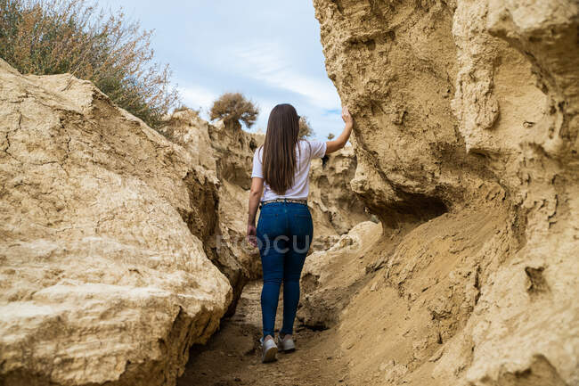 Back view of faceless woman traveler in casual clothing in narrow passage between big brown stones in Bardenas Reales, Navarre, Spain — Stock Photo