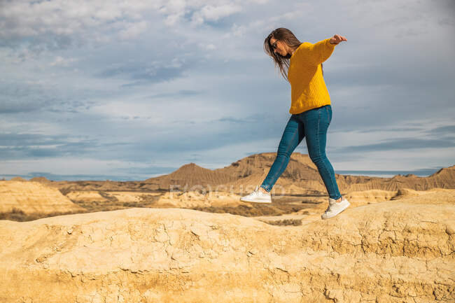 Side view of young female tourist in yellow sweater blue jeans and white sneakers spreading arms for balance while walking along peak of brown hill in Bardenas Reales, Navarre, Spain — Stock Photo