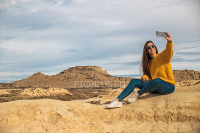 Gioioso giovane viaggiatore femminile in elegante abbigliamento casual sorridente mentre prende selfie sul telefono cellulare con collina marrone e cielo blu sullo sfondo in Bardenas Reales, Navarra, Spagna — Foto stock