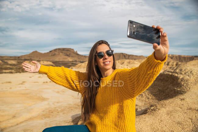 Радісна молода жінка - мандрівниця в стильному повсякденному одязі посміхається, коли робить це на мобільному телефоні з коричневим пагорбом і синім небом на задньому плані в Барденас - Реалес (Наварра, Іспанія). — стокове фото