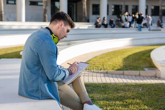 Вид сбоку вдумчивого студента в ярких наушниках, обучающегося на университетской площади и пишущего записную книжку, сидящего на заборе со скрещенными ногами — стоковое фото