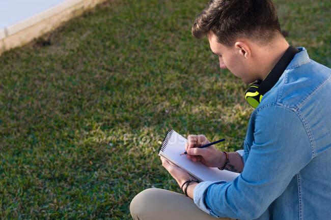 Ragionevole studente maschio in cuffie luminose che studiano in piazza universitaria e scrivono in taccuino seduto sulla recinzione — Foto stock