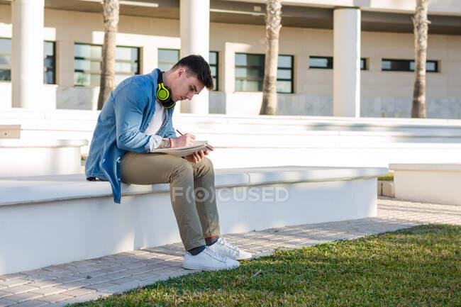 Vue latérale d'un étudiant masculin réfléchi dans un casque lumineux étudiant sur la place de l'université et écrivant dans un carnet assis sur une clôture — Photo de stock