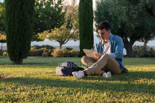Concentrated man with backpack studying writing on notepad while sitting in park grass with crossed legs in sunny day — Stock Photo