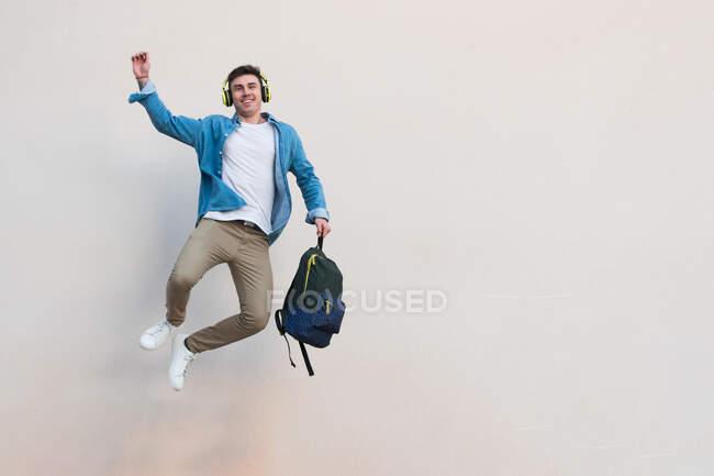 Allegro elegante uomo cuffie con zaino alzando mano celebrando la vittoria e saltando piede di fissaggio sullo sfondo — Foto stock