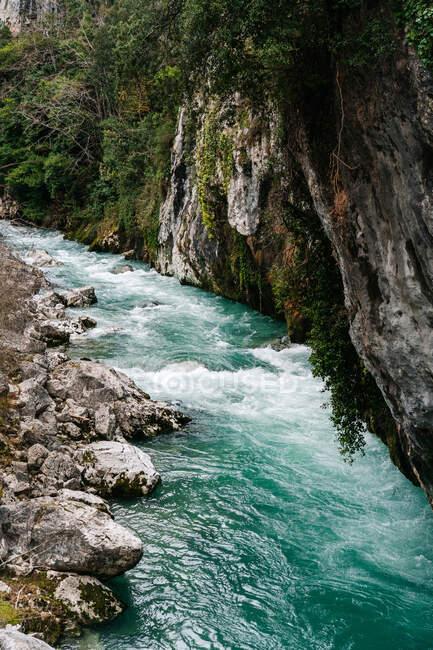 Desde arriba tormentoso río de montaña que fluye a través de montañas rocosas en los picos de Europa, Asturias, España - foto de stock