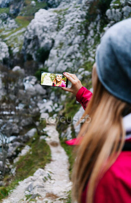 From above smiling woman tourist in red jacket with backpack taking selfie on mobile phone on background of green rocky mountains in village in peaks of Europe, Asturias, Spain — Stock Photo