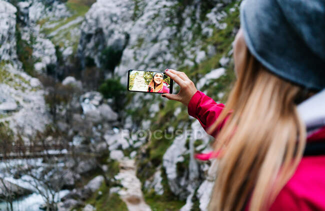 Back view of woman tourist in red jacket with backpack taking selfie on mobile phone on background of green rocky mountains in village in peaks of Europe, Asturias, Spain — Stock Photo