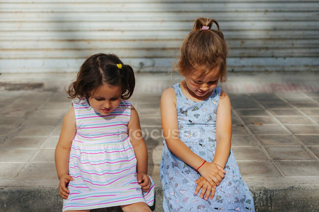 Little girls in summer dresses smiling and talking with each other while sitting on pavement on sunny day in city — Stock Photo