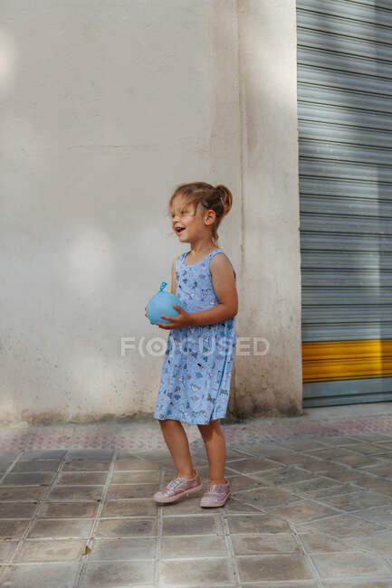 Carino bambina con bomba ad acqua guardando lontano mentre in piedi vicino al marciapiede nella soleggiata giornata estiva sulla strada della città — Foto stock