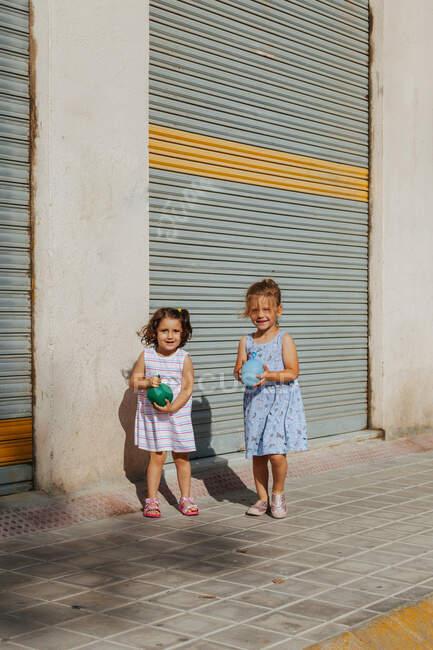 Nette kleine Mädchen mit Wasserbombe schauen in die Kamera, während sie an einem sonnigen Sommertag auf der Stadtstraße in der Nähe des Bürgersteigs stehen — Stockfoto