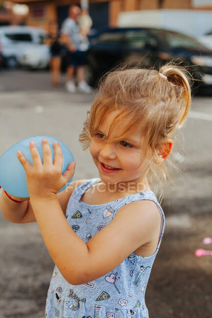 Милая маленькая девочка с водяной бомбой смотрит в сторону, стоя рядом с тротуаром в солнечный летний день на городской улице — стоковое фото