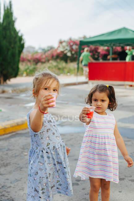 Pequeños amigos en vestidos demostrando tazas con pigmentos brillantes durante el festival en el día de verano en el parque - foto de stock